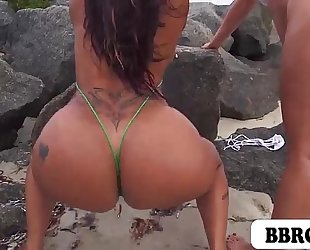 Miss raquel and spicy j showing of their large booties on the beach