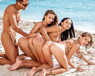 Three beautiful girls pleasuring lucky guy on the beach